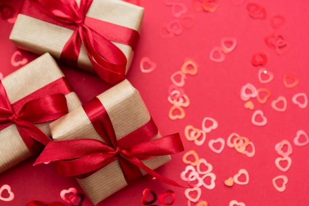 Contenitore di regalo avvolto con la carta kraft e l'arco rosso isolati su fondo rosso. piatto astratto laici.