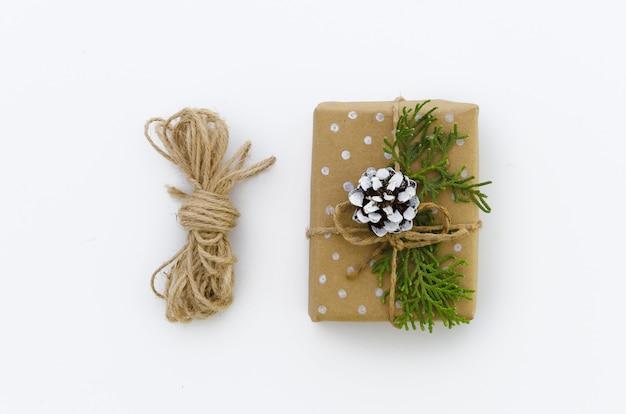 Contenitore di regalo avvolto in carta riciclata marrone e vista superiore corda legata sacco isolato