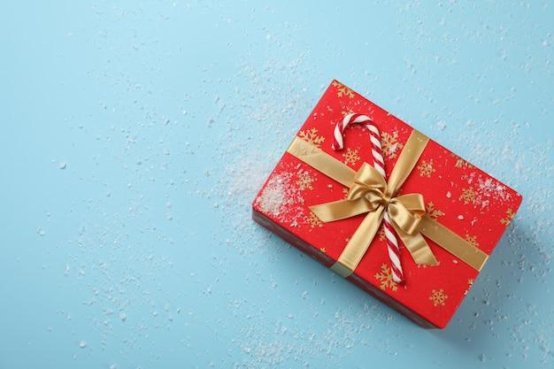 Contenitore di regalo, bastoncino di zucchero e neve su fondo blu, vista superiore