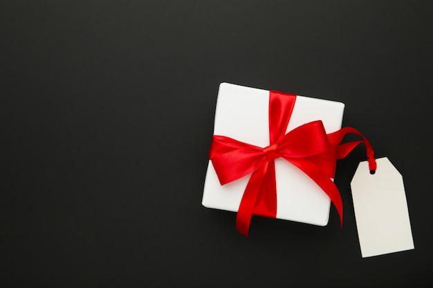 Contenitore di regalo bianco con il nastro rosso con l'etichetta di vendita isolata sul nero
