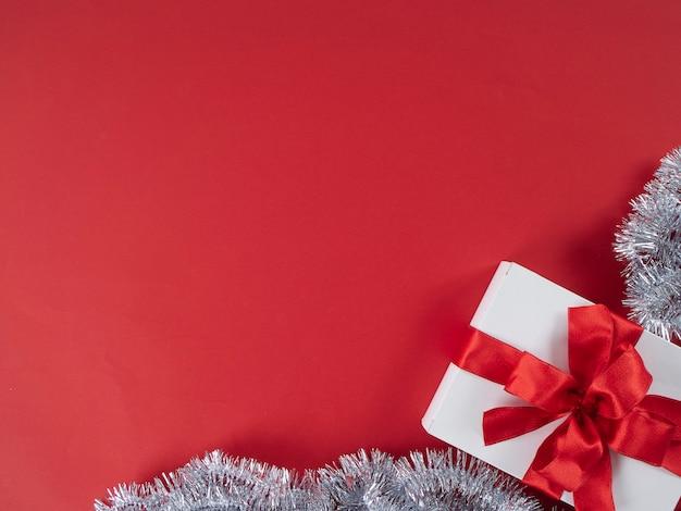 Contenitore di regalo bianco con il nastro rosso su fondo rosso