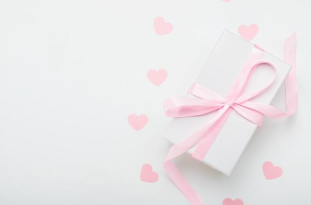 Contenitore di regalo bianco con nastro rosa e cuori su uno sfondo bianco