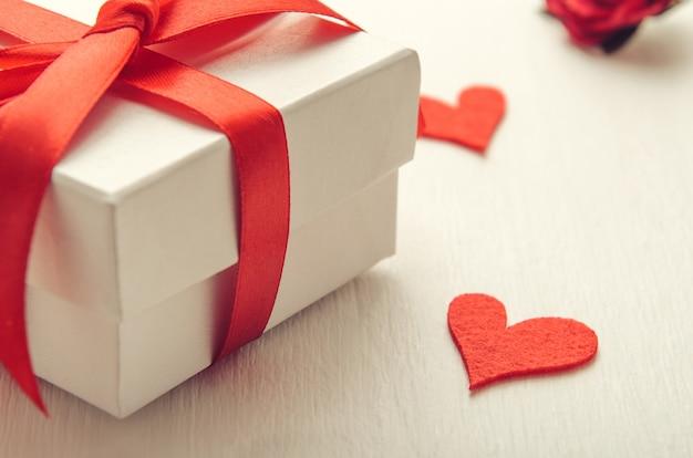 Contenitore di regalo bianco con un arco rosso su fondo bianco con i cuori di feltro.