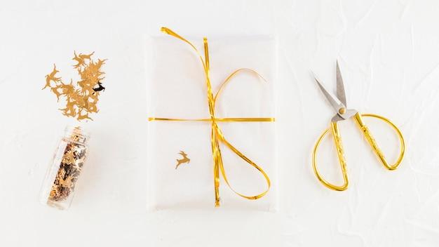 Contenitore di regalo bianco in carta del mestiere vicino a forbici