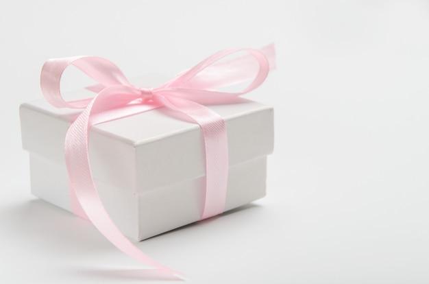 Contenitore di regalo bianco su un bianco con un nastro rosa.