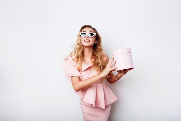 Contenitore di regalo biondo seducente della tenuta della donna e posare in vestito rosa sopra la parete bianca. shopping e celebrando il concetto. occhiali da sole alla moda.