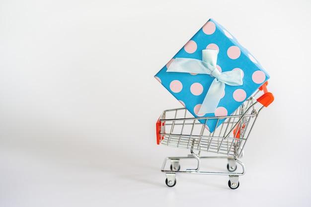 Contenitore di regalo blu e bianco luminoso in un carrello su bianco