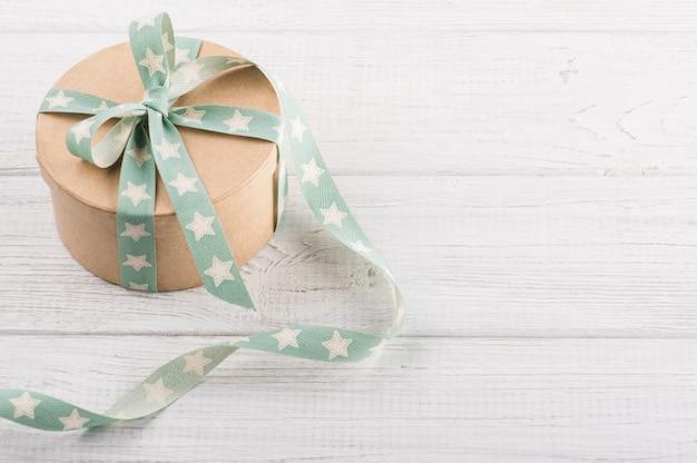 Contenitore di regalo con il nastro della stella sulla tavola rustica bianca