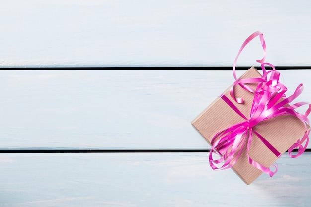 Contenitore di regalo con il nastro rosa piacevole su fondo di legno blu