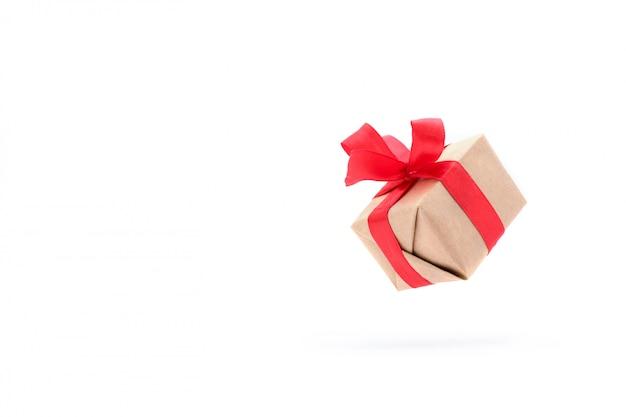 Contenitore di regalo con il nastro rosso isolato in aria su bianco.