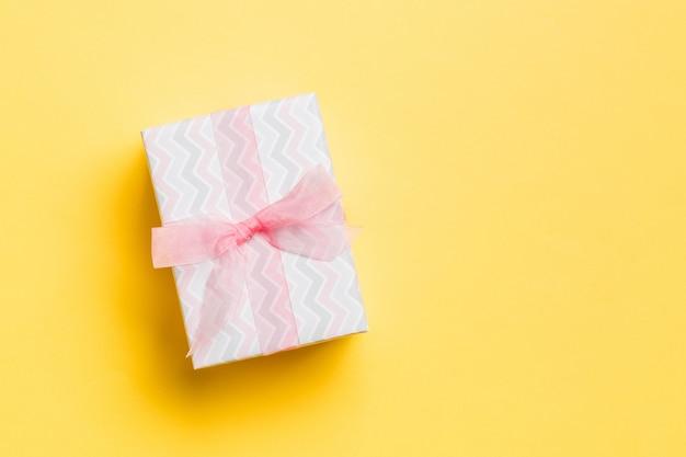 Contenitore di regalo con l'arco rosa per il giorno di natale su giallo