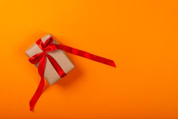 Contenitore di regalo con l'arco sopra fondo arancio.
