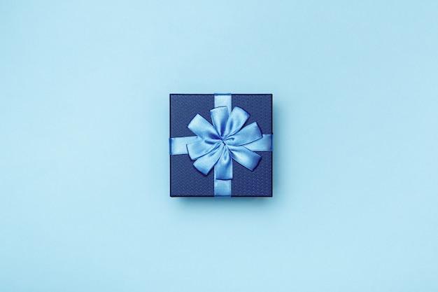 Contenitore di regalo con l'arco su fondo blu