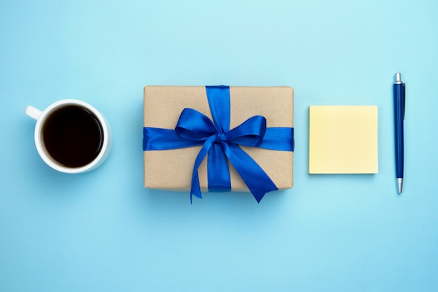 Contenitore di regalo con la tazza di caffè e il blocco note dell'arco del nastro blu isolati su fondo blu.