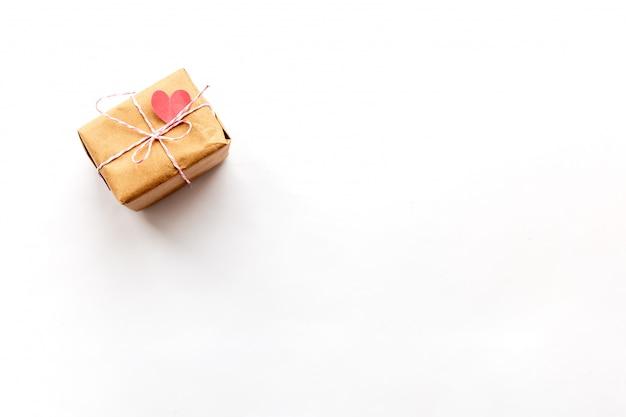 Contenitore di regalo d'annata avvolto con l'arco del nastro rosa su fondo bianco