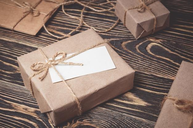 Contenitore di regalo d'annata con l'etichetta in bianco su vecchio di legno.