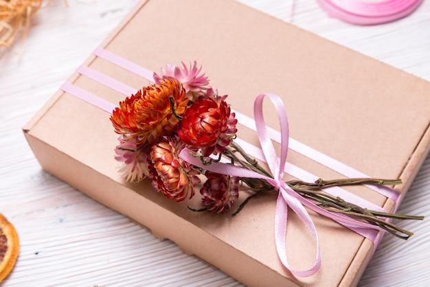 Contenitore di regalo del cartone decorato con i fiori secchi sulla tavola di legno