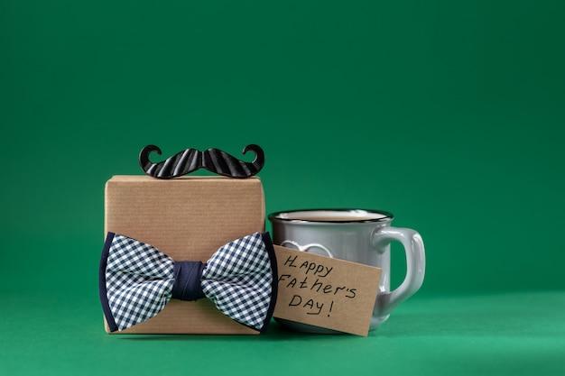 Contenitore di regalo del regalo di festa del papà con il caffè della tazza su verde. concetto attuale di festa.