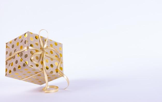 Contenitore di regalo dell'oro del primo piano con un arco dell'oro su fondo bianco. il dono vola nell'aria. santo stefano o concetto di compleanno.