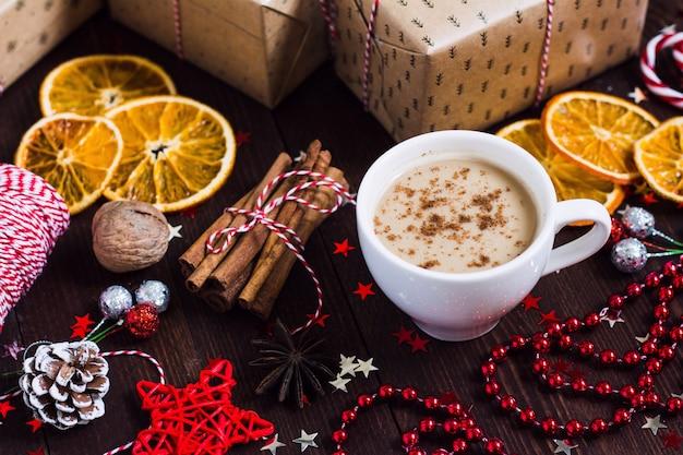 Contenitore di regalo della bevanda della tazza di caffè di festa di natale sulla tavola festiva decorata