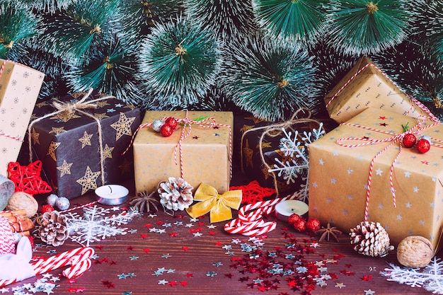 Contenitore di regalo della festa di natale sulla tavola festiva della neve decorata con i rami dell'abete delle pigne