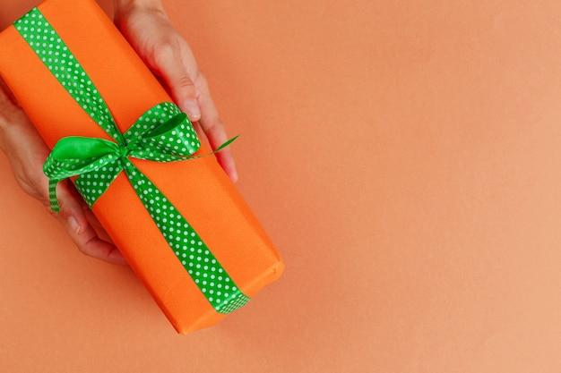 Contenitore di regalo della tenuta della donna sul fondo di colore