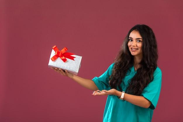 Contenitore di regalo della tenuta della giovane donna con l'arco rosso