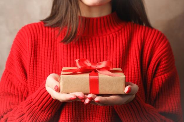 Contenitore di regalo della tenuta della giovane donna, primo piano. spazio per il testo