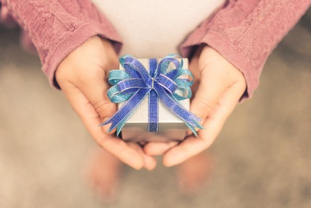 Contenitore di regalo della tenuta della mano della donna di regalo di natale.