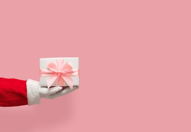 Contenitore di regalo della tenuta della mano di santa claus sul rosa isolato