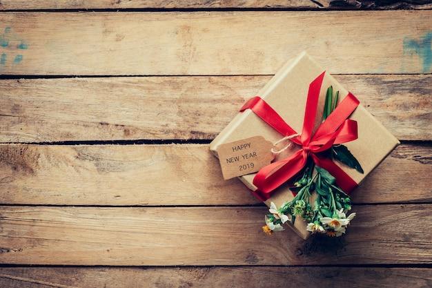 Contenitore di regalo di brown con l'etichetta buon anno 2019 su fondo di legno con lo spazio della copia.