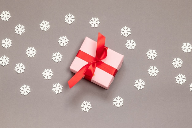 Contenitore di regalo di carta a sorpresa con nastro rosso e fiocchi di neve bianchi su una vista grigia e superiore. nuovo anno. auguri di buon natale.