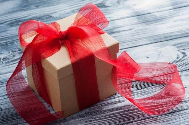 Contenitore di regalo di carta artigianale con fiocco rosso sul tavolo di legno