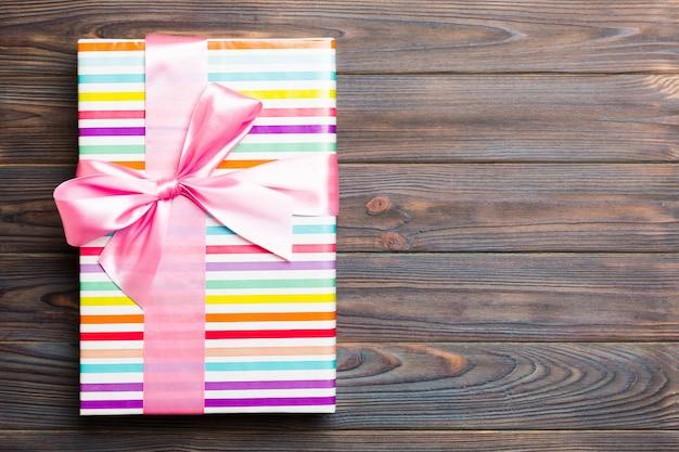 Contenitore di regalo di carta con il nastro colorato su fondo di legno scuro. vista dall'alto con spazio di copia concetto di vacanze di natale