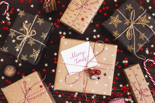 Contenitore di regalo di festa di natale con cartolina buon natale sul tavolo festivo decorato