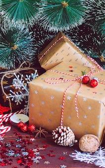 Contenitore di regalo di festa di natale sulla tavola festiva decorata con le noci del bastoncino di zucchero dei rami dell'abete delle pigne