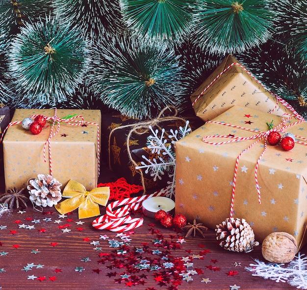 Contenitore di regalo di festa di natale sulla tavola festiva decorata con rami di abete di pigne