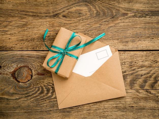 Contenitore di regalo di festa, legato con nastro verde, busta aperta di carta kraft con cartolina