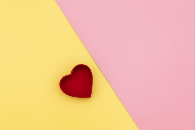 Contenitore di regalo di forma del cuore su fondo giallo e rosa