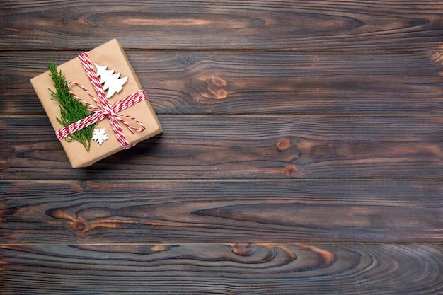 Contenitore di regalo di natale avvolto in carta riciclata, con la vista superiore del nastro con lo spazio della copia su fondo rustico. concetto di vacanza