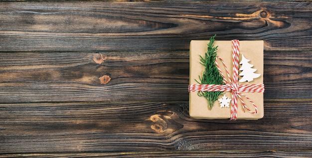 Contenitore di regalo di natale avvolto in carta riciclata su fondo di legno, vista superiore