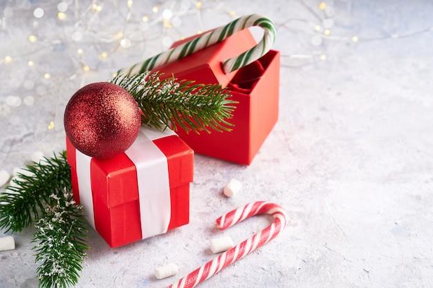 Contenitore di regalo di natale, caramelle, rami di abete, giocattolo dell'albero di natale su sfondo chiaro. concetto di natale e capodanno copia spazio.