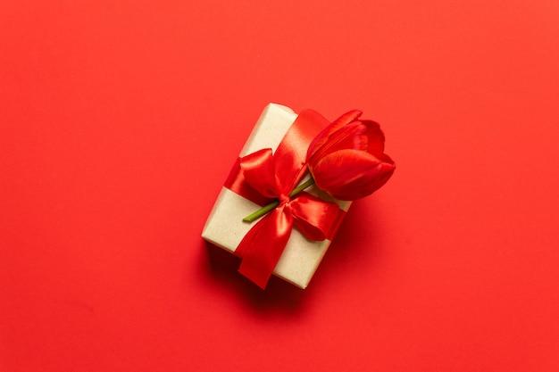 Contenitore di regalo di natale con il fiore rosso del tulipano legato con l'arco su rosso