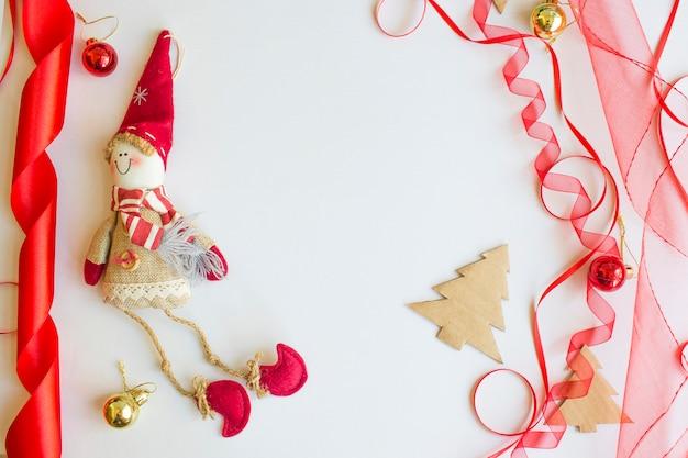 Contenitore di regalo di natale con il nastro rosso e la filiale attillata sul bianco sopra le pigne, vista isolata e superiore