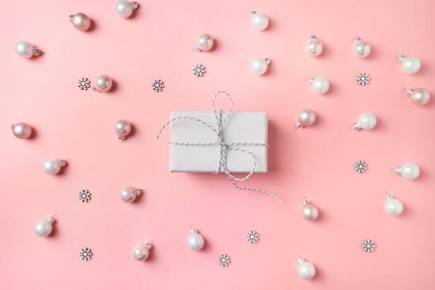 Contenitore di regalo di natale con le sfere bianche sul colore rosa. vista dall'alto. xmas. felice anno nuovo.