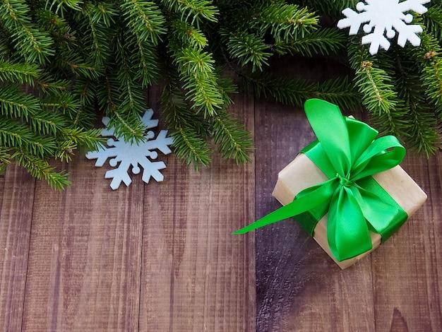 Contenitore di regalo di natale con nastro rosso su legno, regali di natale con decorazioni