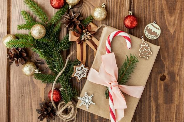 Contenitore di regalo di natale, decorazione e ramo di albero di abete sulla tavola di legno. vista dall'alto con copyspace