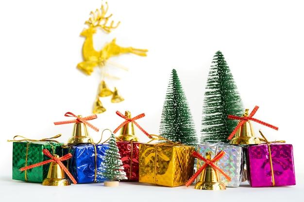 Contenitore di regalo di natale e albero con campane d'oro, pigne su sfondo bianco