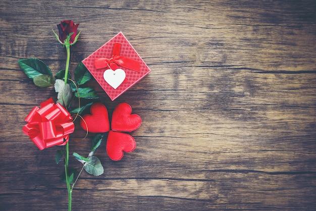 Contenitore di regalo di san valentino rosso su legno cuore rosso san valentino rosa rossa fiore e presente fiocco di nastro scatola