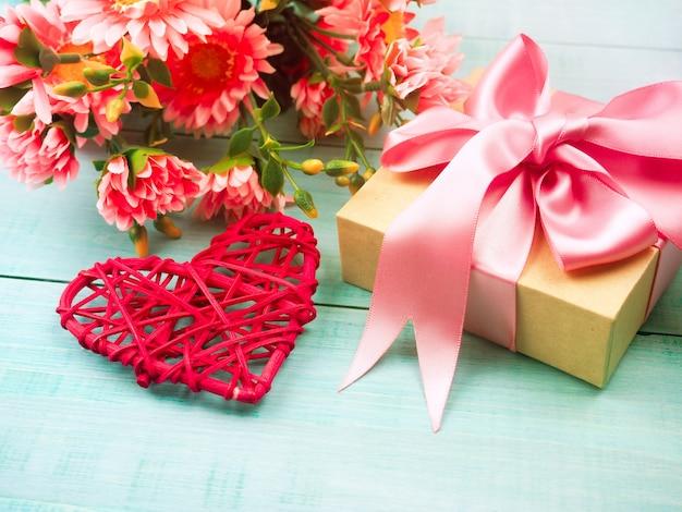 Contenitore di regalo e cuore di vimini rosso su un blu di legno